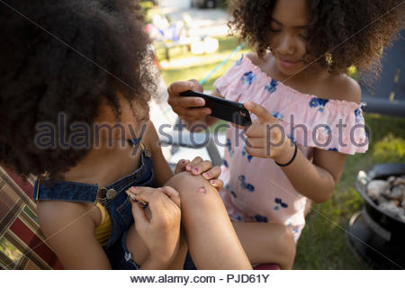 Girl with camera phone photographing sister with scraped knee - Stock Photo