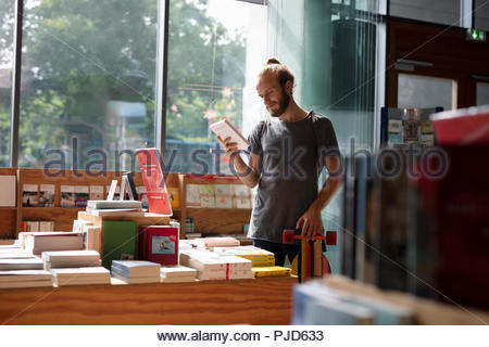 Man with skateboard shopping in bookstore - Stock Photo