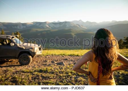 Woman looking at sunny mountain view near SUV, Alberta, Canada - Stock Photo