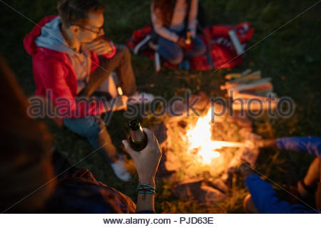 Friends drinking beer around campfire - Stock Photo