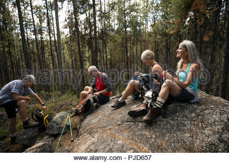 Mature couples taking a break from hiking, resting on forest rock - Stock Photo