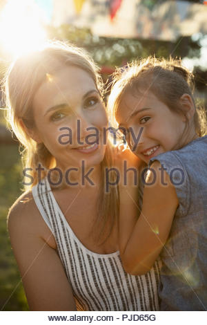 Portrait mother and daughter in sunny park - Stock Photo