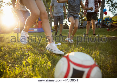 Family playing soccer in sunny park - Stock Photo