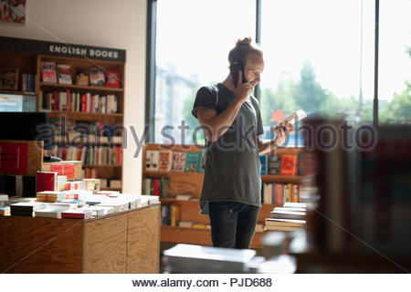 Man talking on cell phone and shopping in bookstore - Stock Photo
