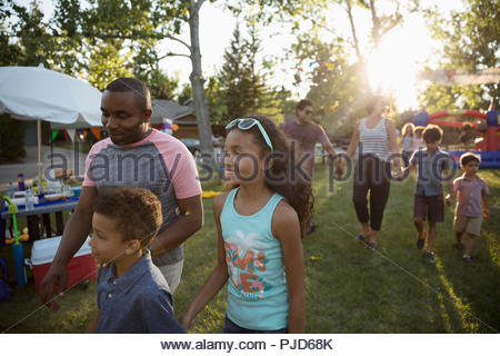 Family at summer neighborhood block party in park - Stock Photo