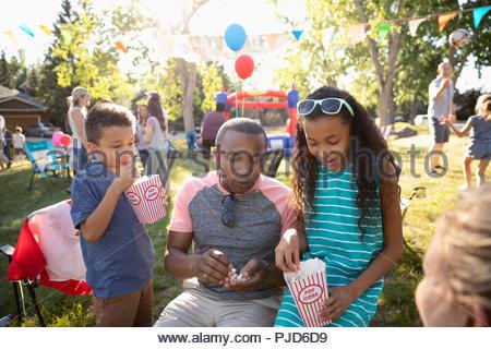 Family eating popcorn, enjoying summer neighborhood block party in park - Stock Photo