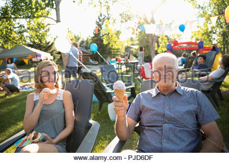 Portrait carefree senior man eating ice cream cone with daughter at summer neighborhood block party in park - Stock Photo