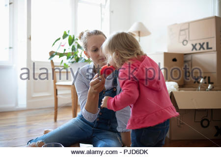Mother and daughter eating watermelon, taking a break from moving in - Stock Photo