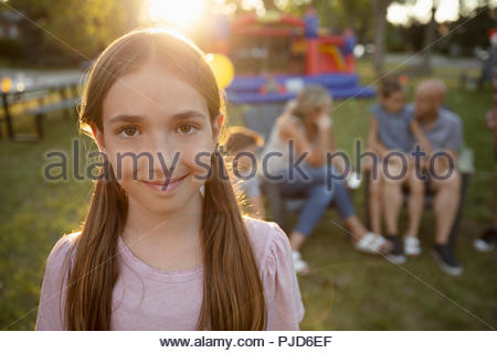 Portrait smiling, confident girl in sunny park with family - Stock Photo