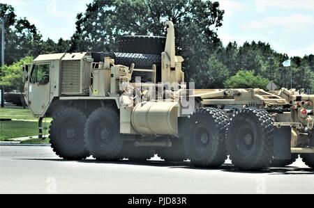 Soldiers operate an M1120 Heavy Expanded Mobility Tactical Truck (Load-Handling System) on the cantonment area during installation training operations July 24, 2018, at Fort McCoy, Wis. The truck is an eight-wheel drive, diesel-powered, tactical truck used by the U.S. military and others. In the Army, the M1120 can be equipped with several different styles of flatracks for the load handling system. - Stock Photo