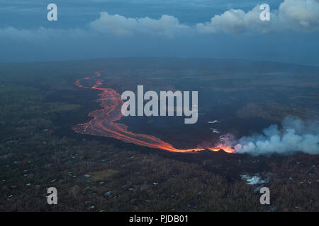 river of hot lava flows from fissure 8 in Kilauea Volcano east rift zone in Leilani Estates subdivision, near Pahoa, toward the sea at Kapoho, Hawaii - Stock Photo