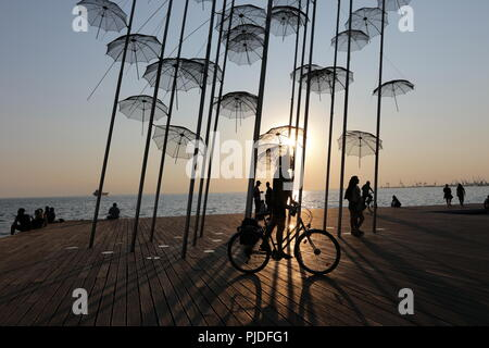 Woman cycling past the Umbrellas, a permanent metallic installation by George Zoggolopoulos, in the northern Greek port city of Thessaloniki - Stock Photo