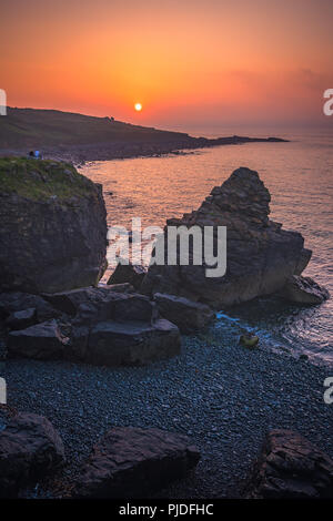 St. Ives, England -  May 2018 : Couple sitting on a rock and admiring sunset over the Cornish coast, Cornwall - Stock Photo