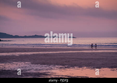 St. Ives, England -  May 2018 : Family walking on the empty beautiful Porthmeor Beach at sunset, Cornwall, UK - Stock Photo