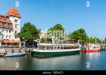 Rostock, Germany - May 26, 2017: Colorful harbor tour ship and fishing boats resting in the peaceful canal on this spring hot day in Warnemunde, Rosto - Stock Photo