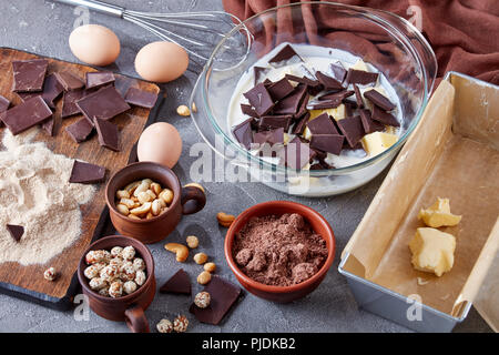 making chocolate pound cake from buckwheat flour, eggs, dark chocolate, nuts, milk and butter. ingredients, whisk, metal baking mold on a concrete tab - Stock Photo