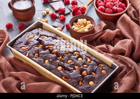 close-up of chocolate buckwheat pound cake with nuts and raspberries in a metal baking mold on a concrete table with cup of coffee and brown tissue, v - Stock Photo