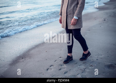 Young woman walking on beach, leaving footprints in wet sand, low section - Stock Photo