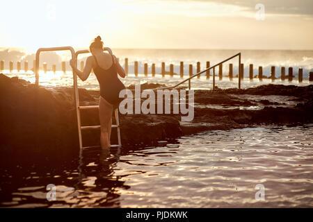 Woman climbing up coastal pool ladder, Las Palmas, Gran Canaria, Canary Islands, Spain - Stock Photo