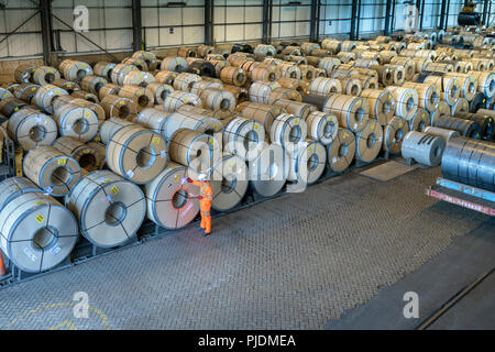 Worker with rows of sheet steel in storage at port - Stock Photo