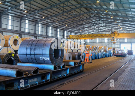 Workers with rows of sheet steel in storage at port - Stock Photo