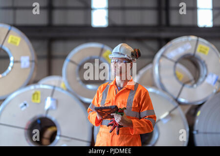 Portrait of worker using digital tablet by rows of sheet steel in storage at port - Stock Photo