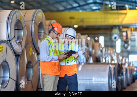 Workers using digital tablet by rows of sheet steel in storage at port - Stock Photo