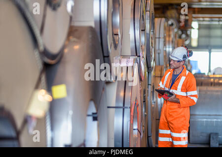 Worker using digital tablet by rows of sheet steel in storage at port - Stock Photo
