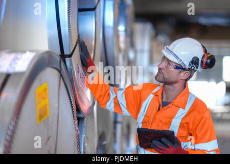 Worker using digital tablet to inspect rows of sheet steel in storage at port - Stock Photo