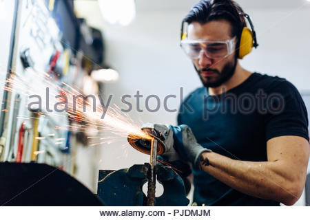 Young man using angle grinder on metal in workshop - Stock Photo