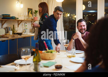 Friends talking, man setting table at dinner party - Stock Photo