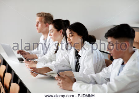 Students at desk in science class - Stock Photo