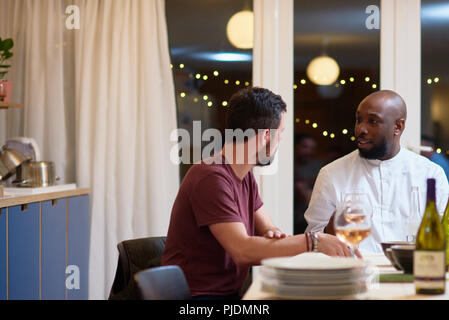 Friends talking at dinner party - Stock Photo