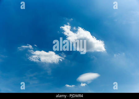 Little fluffy clouds making their way through the sky on a beautiful summers day. - Stock Photo