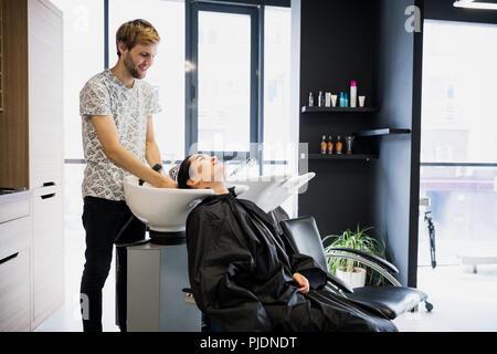 Beautiful young girl washing her head in a beauty salon - Stock Photo