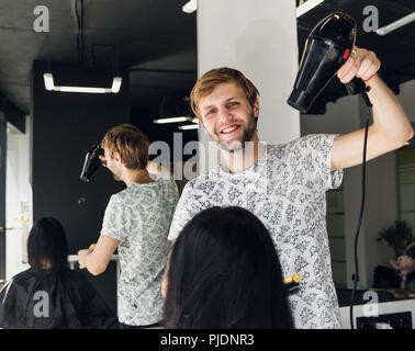 Professional smiling male stylist blow drying woman's hair with a dryer in salon - Stock Photo