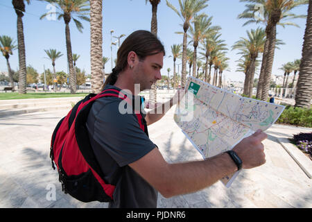 Close portrait of man looking on map in Jerusalem - Stock Photo
