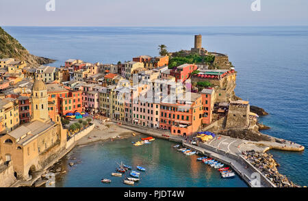 Italy, Liguria, Cinque Terre, Vernazza, View of the Church of Santa Margherita di Antiochia and Castello Doria with its Belforte Tower above the harbour from high up on the Sentiero Azzurro or Blue Trail which is the famous hiking trail that links the 5 towns. - Stock Photo