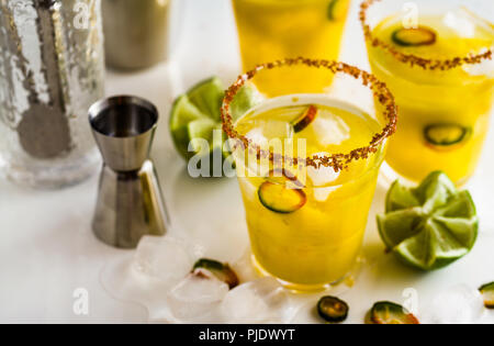 cocktail margarita of tequila, mango juice, hot pepper and lime on the table. bar accessories - Stock Photo