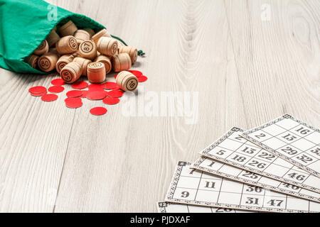 Game cards, wooden lotto barrels with green bag and red chips for a game in lotto on grey board. Board game lotto - Stock Photo