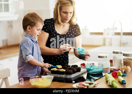 Beautiful child and mother baking - Stock Photo