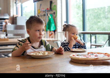 kids eat pizza and meat dumplings at cafe. children eating unhealthy food indoors. Siblings in the cafe, family holiday concept. - Stock Photo