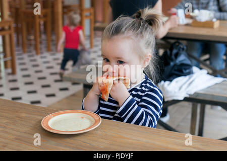 Cute little 2 years girl eating pizza in the restaurant - Stock Photo