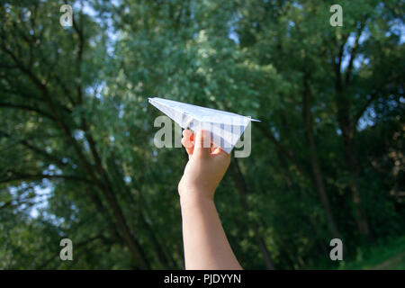 Taking flight! Hand holding paper airplane in the sky and green garden, concept of summer, childhood, dreaming - Stock Photo