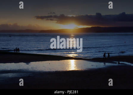 A winter sunset on a calm day at Exmouth beach in Devon, England, a family enjoy a last walk at sunset - Stock Photo