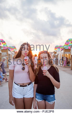 Two teenage girls stroll through an open-air market and have a refreshing red drink. - Stock Photo