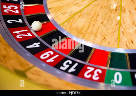 Roulette table in casino. Ball in the rotating gambling machine. Wooden roulette wheel. - Stock Photo