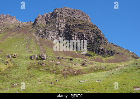 A view looking up at Stac Pollaidh, Scotland, from the south side, car park path, with three hill walkers ascending the mountain track to the rocks - Stock Photo