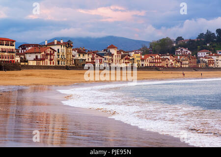Traditional basque timber houses facing sand beach in Saint Jean de Luz, a resort town on Atlantic coast, Bay of Biscay, France - Stock Photo