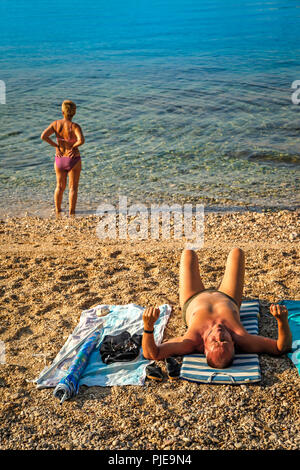 A woman at water's edge stares out over the Adriatic on the Croatian island of Krk at the resort of Baska, while man sunbathes on beach - Stock Photo